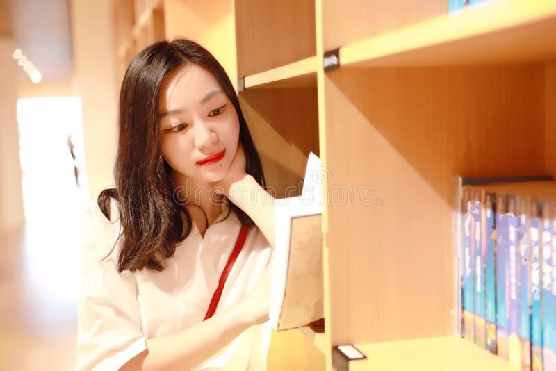 Slutet upp den asiatiska kinesiska härliga nätta gulliga kvinnaflickastudenten Teenager läste boken i bokhandelarkivleende royaltyfria bilder