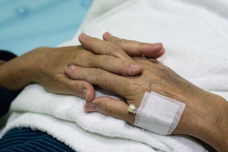 Slutet upp den gamla kvinnliga handen av den äldre patienten med den intravenösa kateter för injektion pluggar i hand arkivfoto