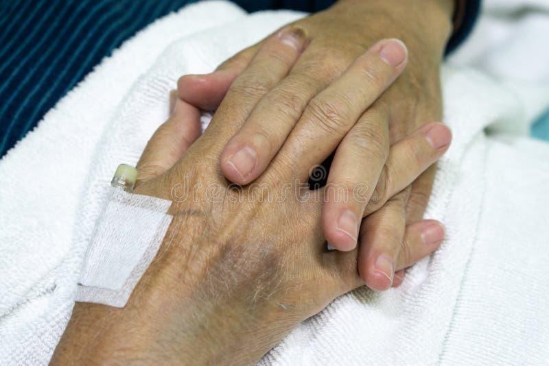 Slutet upp den gamla kvinnliga handen av den äldre patienten med den intravenösa kateter för injektion pluggar i hand royaltyfria foton