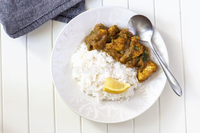 Slutet upp den traditionella indiska smörhönacurry och citronen tjänade som med den vita plattan för kokta ris Top besk?dar arkivfoton