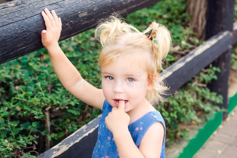 Slutet upp det Blondy lilla barnet behandla som ett barn flickan som ser kameran och sätter hennes finger in i hennes mun - ett a royaltyfri bild