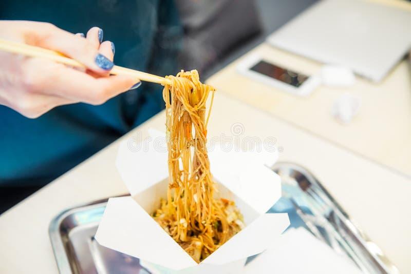 Slutet upp flickan som äter asiatisk fastfood, wokar nudlar från den pappers- asken i kafé under hennes lunchavbrott Läcker kines fotografering för bildbyråer