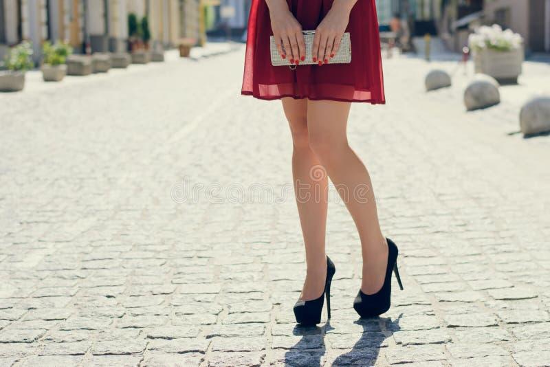 Slutet upp fotoet av logh för kvinna` s lägger benen på ryggen mot sikten av staden Sh royaltyfria foton