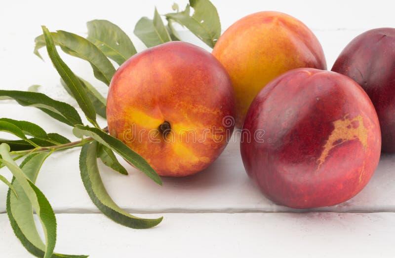 Slutet upp fotoet av nektarinen bär frukt på den lantliga vita wood tabellen arkivbild
