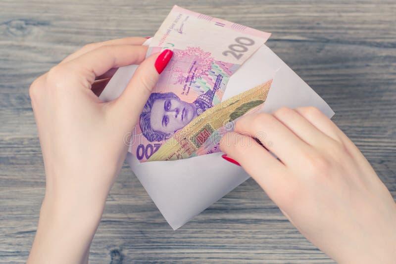 Slutet upp fotoet för den bästa sikten av kvinna` s räcker att ta ukrainska pengar arkivfoton