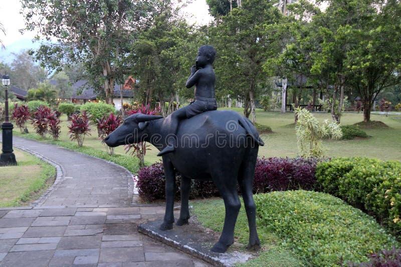 Slutet upp grodor spelar musik i olikt stylesChildren spela flöjten, och buffeln rider på det Manohra hotellet arkivfoton