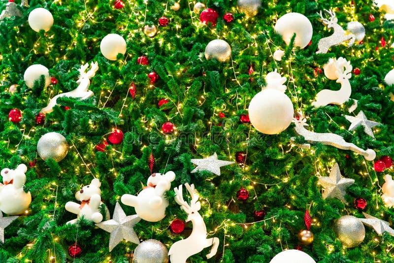 Slutet upp julgrangarnering med rött, guld-, försilvrar, och vita bollar, försilvrar stjärnan och den vita renen extra bakgrundsf royaltyfri fotografi