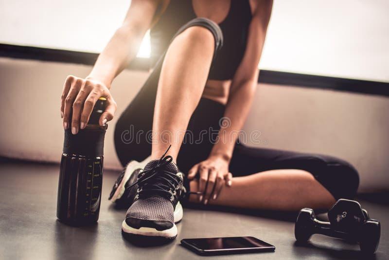 Slutet upp kvinnaövningsgenomkörare i inomhus konditionidrottshallavbrott kopplar av efter sportutbildning med telefonen och prot royaltyfri foto