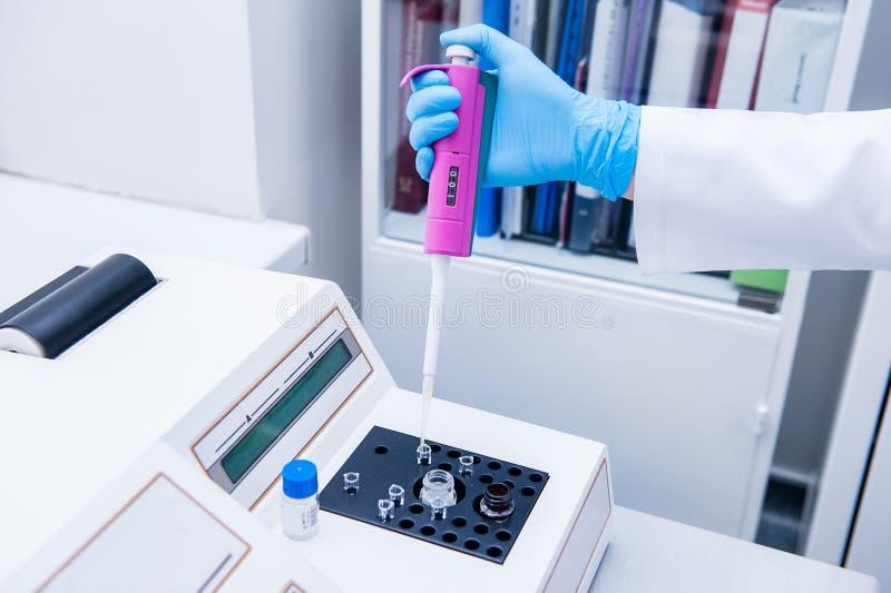 Slutet upp kvinnaforskarekemist med provröret i hans hand gör analysen i det moderna laboratoriumet arkivfoto
