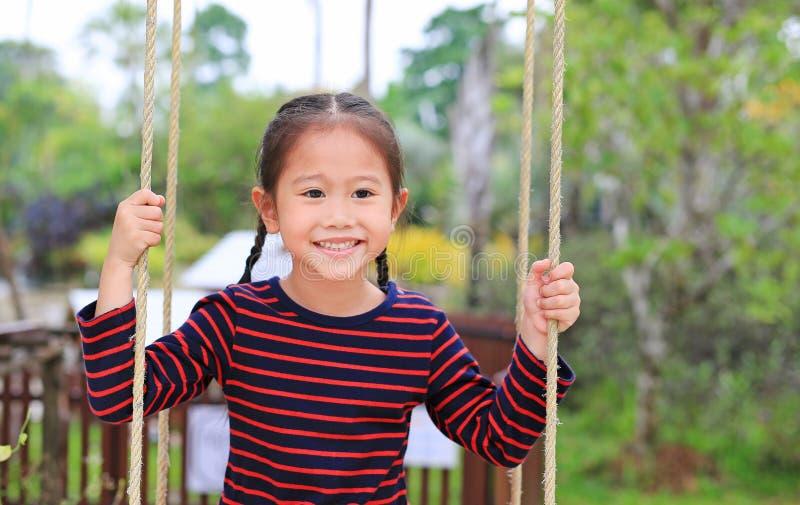 Slutet upp lycklig liten asiatisk barnflickalek och att sitta på gungan i naturen parkerar arkivbilder