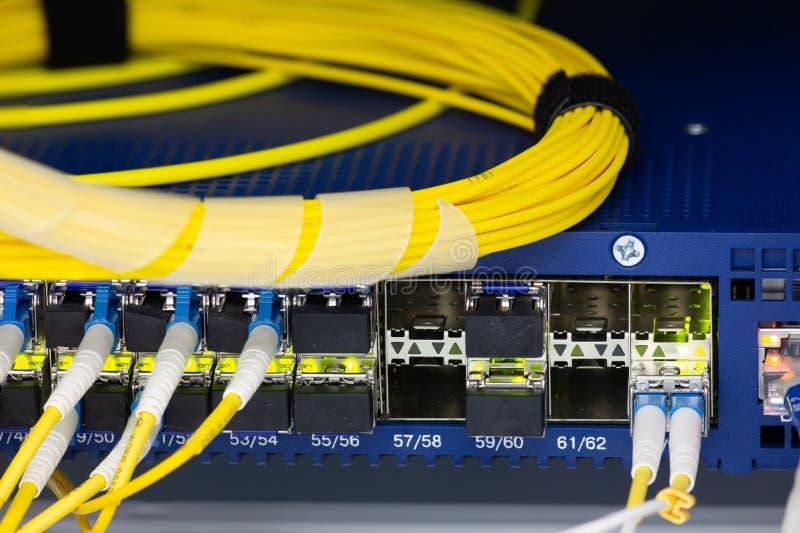 Slutet upp optiskt för fiber i serverrum, nätverkskablar som installeras i kuggeabstrakta begreppet, avbildar för bruk som en bak arkivbilder