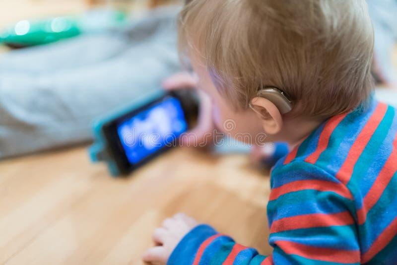 Slutet upp på hörapparat weared förbi behandla som ett barn arkivfoto