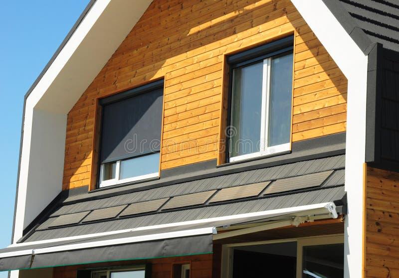 Slutet upp på hus förblindar solskyddsyttersida Windows i trävägg för ny modern passiv husfasad med stängda slutare och royaltyfria bilder