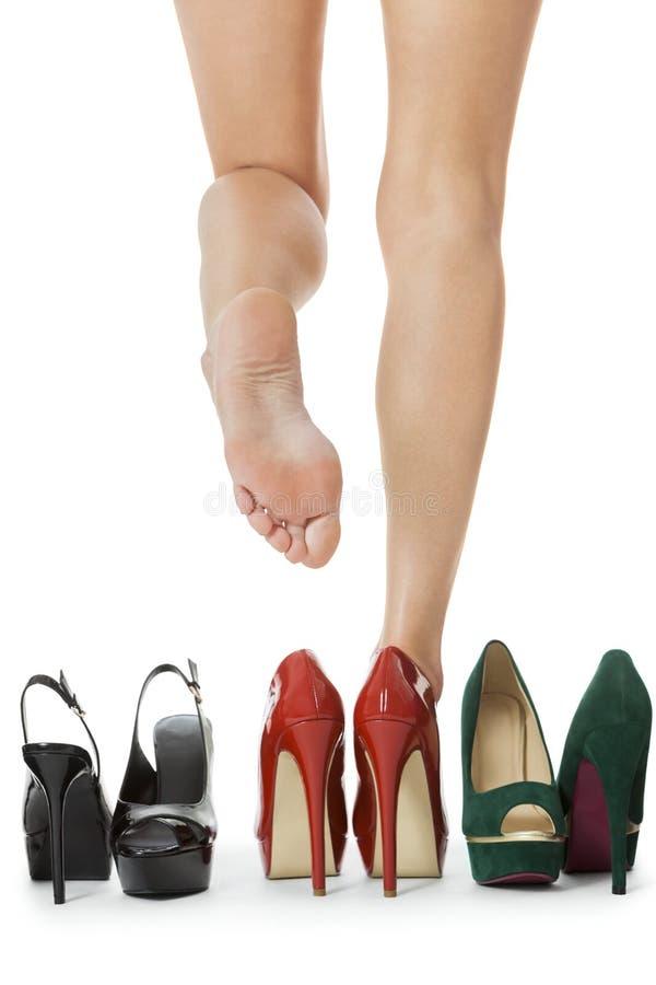 Slutet upp prickfria kvinnaben i glansig röd hög häl skor anseende arkivfoto