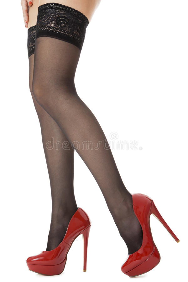 Slutet upp prickfria kvinnaben i glansig röd hög häl skor anseende royaltyfri fotografi