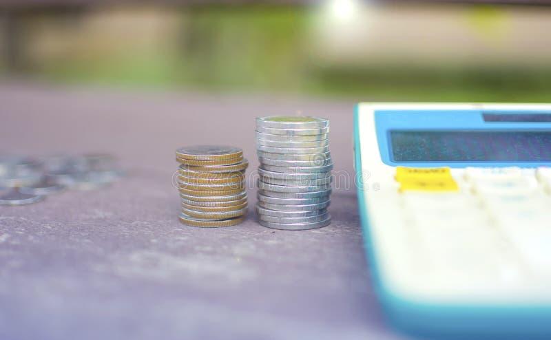 Slutet upp resningmynt två högar av thailändska mynt för pengarsilver staplar, och räknemaskinen låg på en trätabell med linssign arkivbild