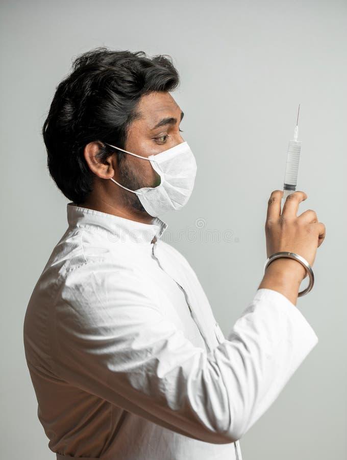 Slutet upp sportrait för sidosikt av den indiska doktorn med injektionssprutan förbereder sig för injektion arkivbilder