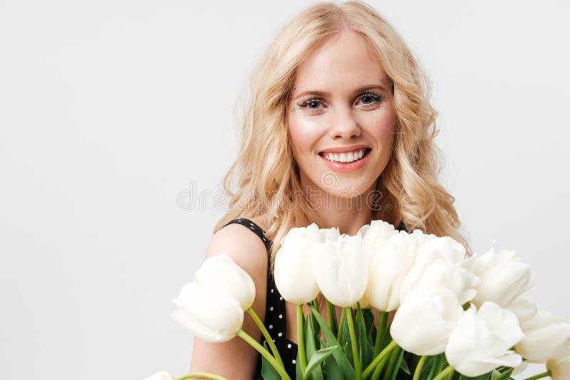 Slutet upp ståenden av den blonda kvinnan som poserar med buketten, blommar royaltyfria foton