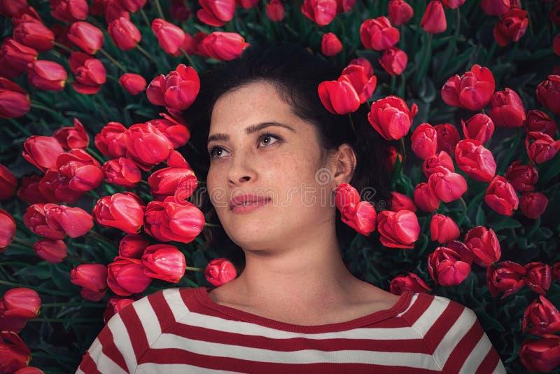 Slutet upp ståenden av den unga härliga flickakvinnan med rött brunt hår som ligger på gräs med den röda tulpan, blommar runt om  arkivfoto