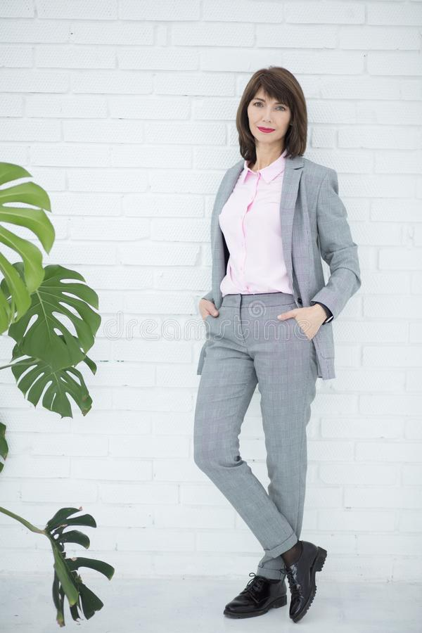 Slutet upp ståenden av en allvarlig affärskvinna i grå färger passar anseende i staden arkivfoton