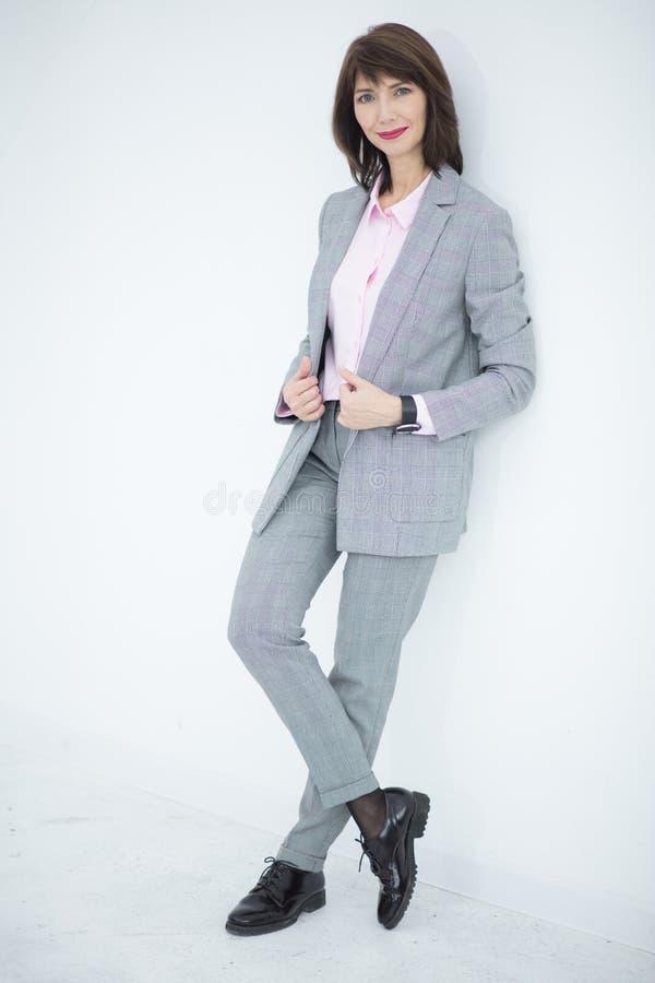 Slutet upp ståenden av en allvarlig affärskvinna i grå färger passar anseende i staden royaltyfria bilder