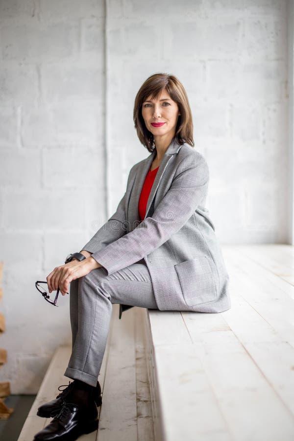 Slutet upp ståenden av en allvarlig affärskvinna i grå färger passar anseende i staden fotografering för bildbyråer