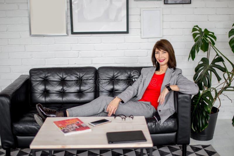 Slutet upp ståenden av en allvarlig affärskvinna i grå färger passar anseende i staden royaltyfri foto