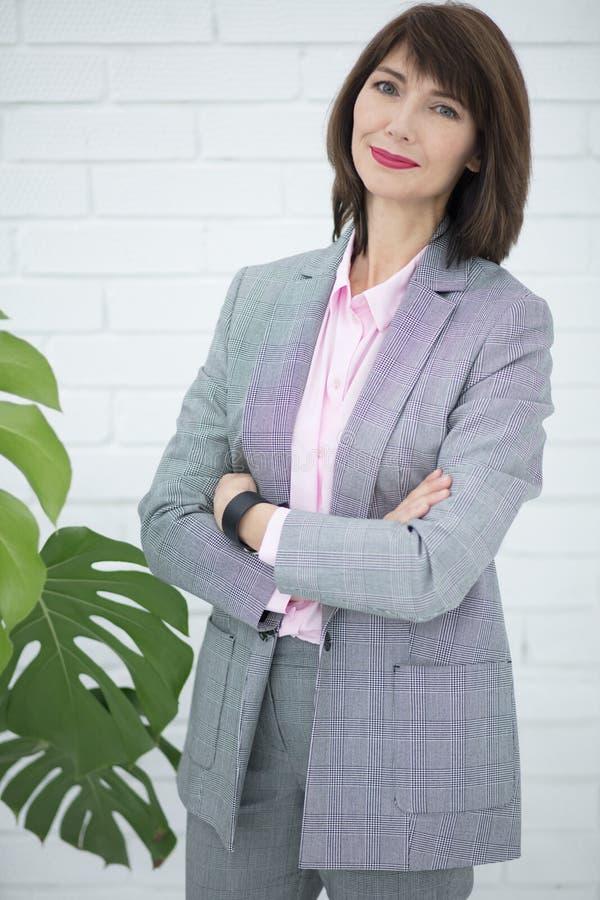 Slutet upp ståenden av en allvarlig affärskvinna i grå färger passar anseende i staden royaltyfri fotografi