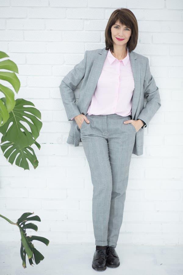 Slutet upp ståenden av en allvarlig affärskvinna i grå färger passar anseende i staden royaltyfria foton