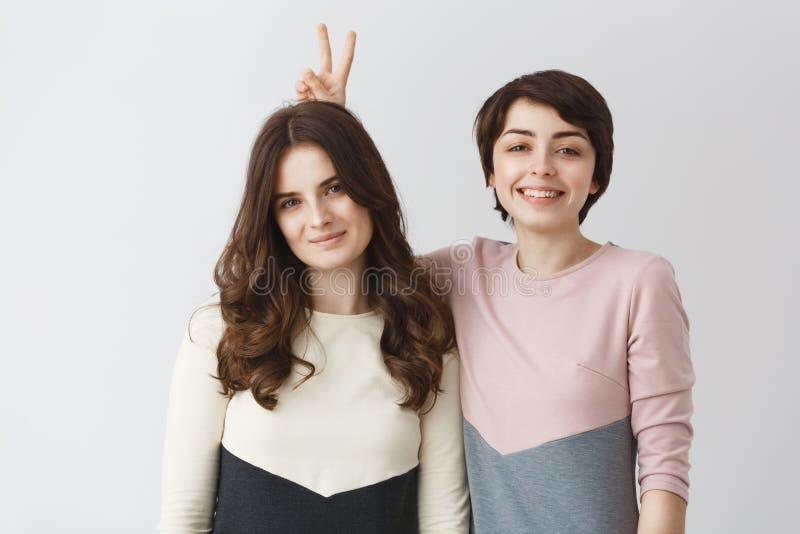 Slutet upp ståenden av unga lyckliga lesbiska par med mörkt hår, i att matcha, beklär att le och att ha gyckel som poserar för fo fotografering för bildbyråer