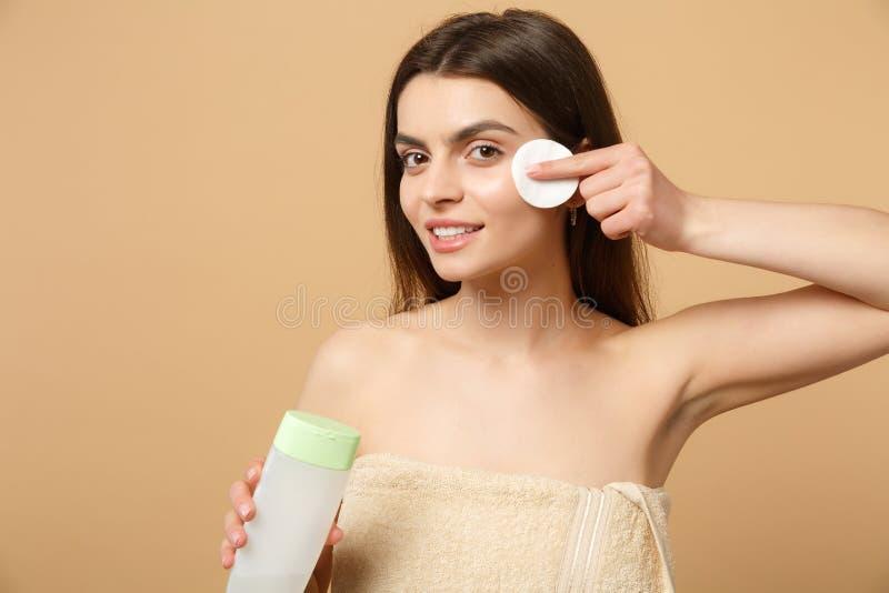 Slutet upp 20-tal för kvinna för brunetthalva naken med perfekt hud som tar bort nakenstudie, utgör isolerat på beige pastellfärg royaltyfria bilder