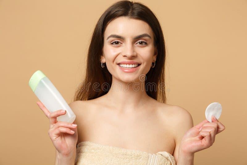Slutet upp 20-tal för kvinna för brunetthalva naken med perfekt hud som tar bort nakenstudie, utgör isolerat på beige pastellfärg royaltyfri fotografi