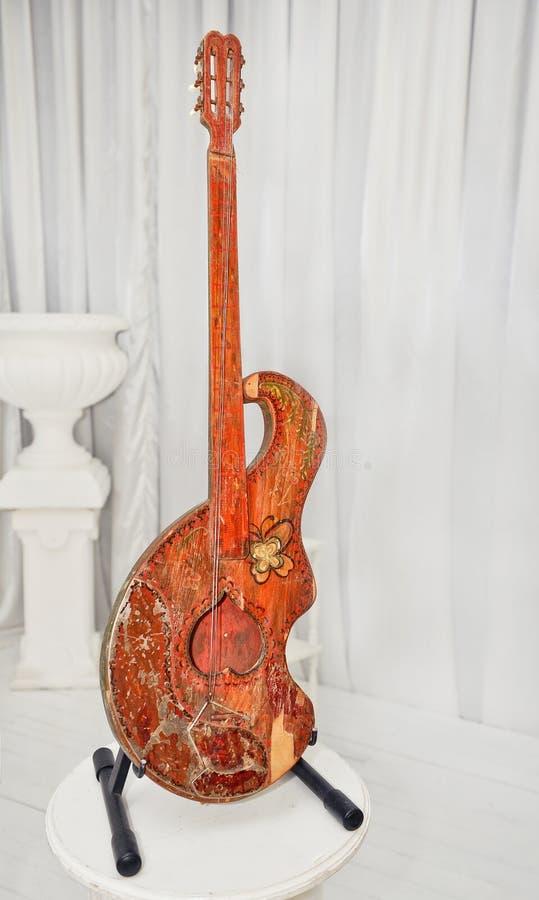 Slutet upp violoncellen som isoleras på vit, hänger upp gardiner i bakgrund arkivfoto