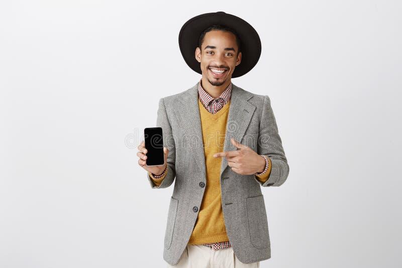 Slutligen ny modell av smartphonen Positiv lycklig grabb i stilfull dräkt och hatten som visar smartphonen och pekar på apparaten fotografering för bildbyråer