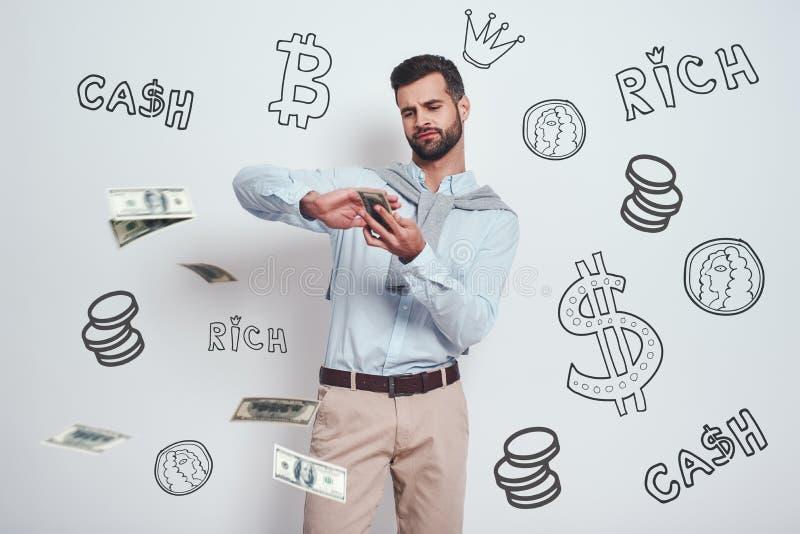 Slutligen rich Den säkra skäggiga mannen sprider dollar, medan stå mot grå bakgrund med olikt klotter arkivbild