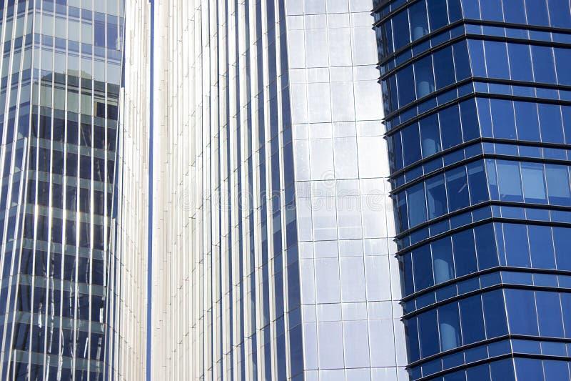 Slutskottet av ett par av kopplar samman företags blåa kontorsbyggnader med en randig design royaltyfri foto