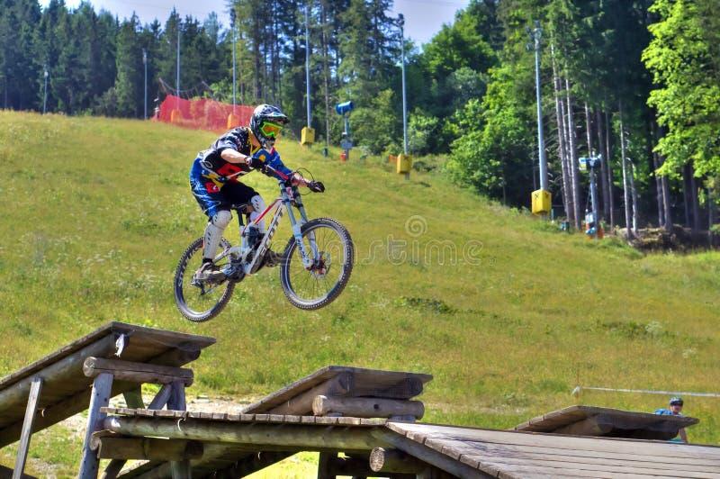Sluttande cykelryttare som hoppar av jordning på mountainbikeloppet royaltyfri bild