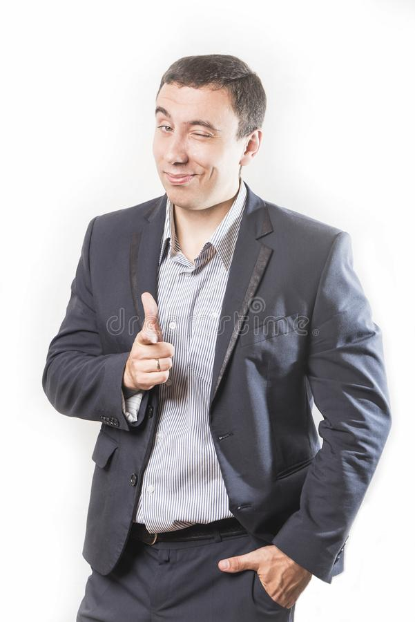 Sluwe en zakenman die, die wijsvinger tonen in camera glimlachen knipogen, op witte achtergrond wordt geïsoleerd stock afbeelding