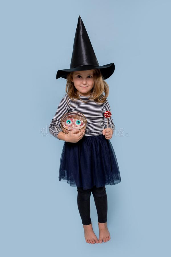 Sly girl in a witch costume at Halloween holds candy and lollipop royalty free stock image