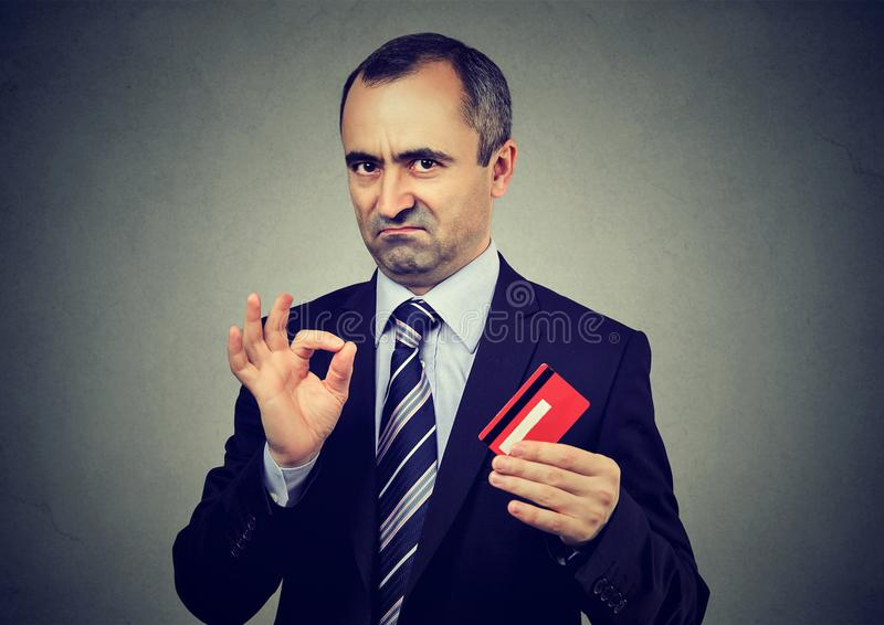 Sly liar mature businessman employee reassuring their credit card is the best stock image
