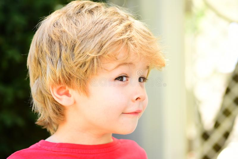 Sly playful baby boy. Funny child with cute hairstyle. Smart kid with idea, sly look. Children face. stock photos