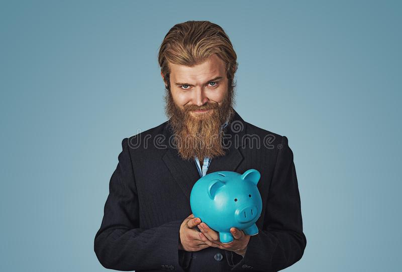 Sly Young man holding piggy bank plotting stock images