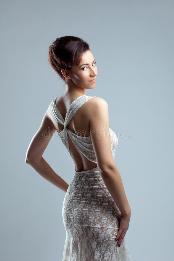 Slyly smiling girl posing in erotic lacy dress. Portrait of slyly smiling girl posing in erotic lacy dress stock images
