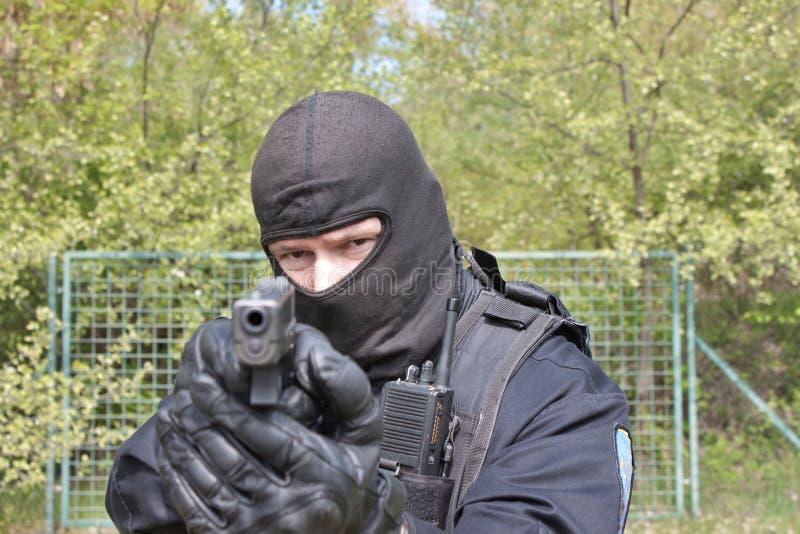 Smälla till polisen som pekar ett vapen på kameran arkivfoton