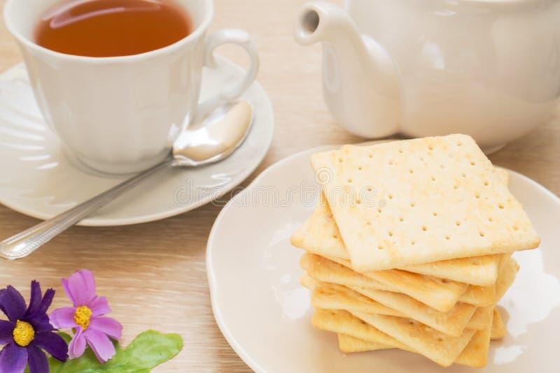Smällare, kopp te och kruka arkivfoton