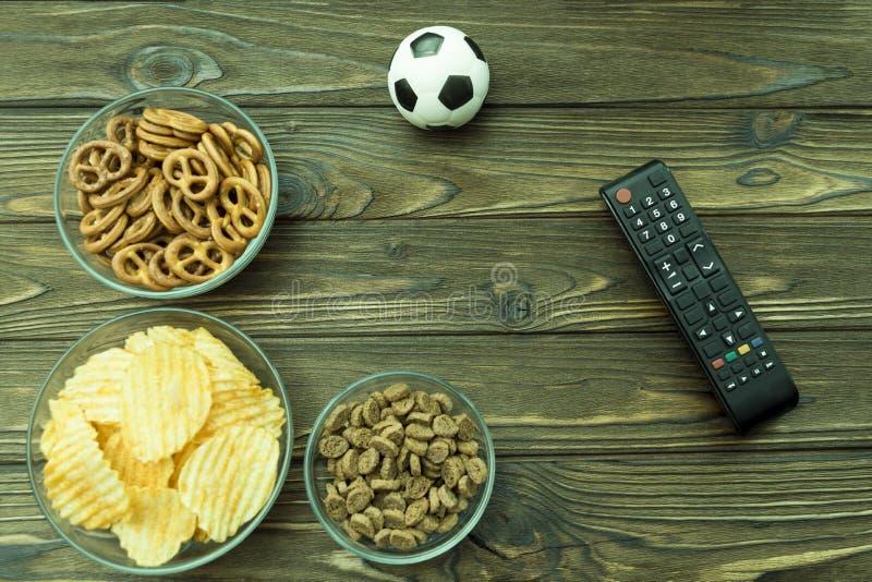 Smällare potatischiper till öl, fjärrkontroll från TV:N, fotbollboll fotografering för bildbyråer