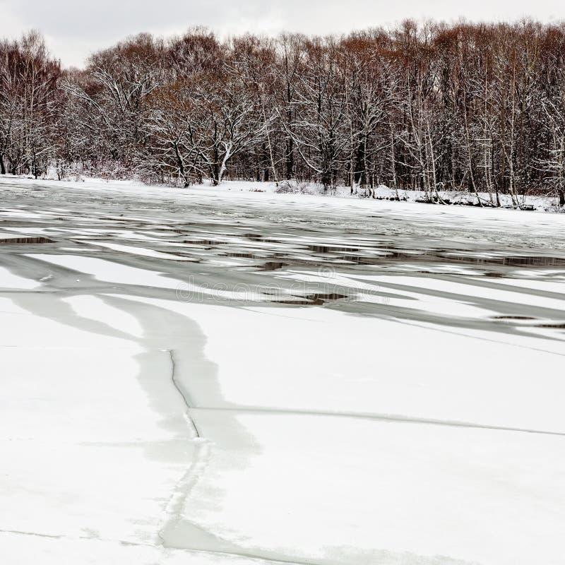 Smältande is på den djupfrysta floden arkivfoton
