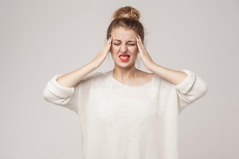 Smärta begreppet, dåliga känslor Den blonda kvinnan har en migrän och en hea royaltyfri fotografi