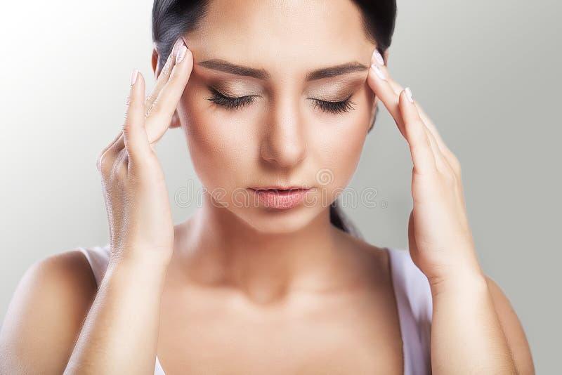 smärta En härlig kvinna på en grå bakgrund, spänning och huvudvärk med migränhuvudvärker, brottades hon med smärtar, en stor ståe royaltyfri bild