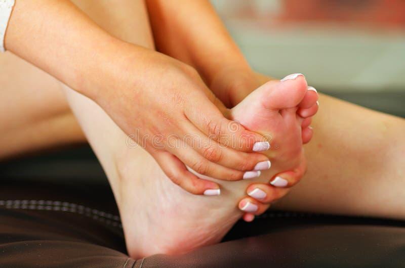 Smärta i foten, auto massage av kvinnlig fot arkivfoton